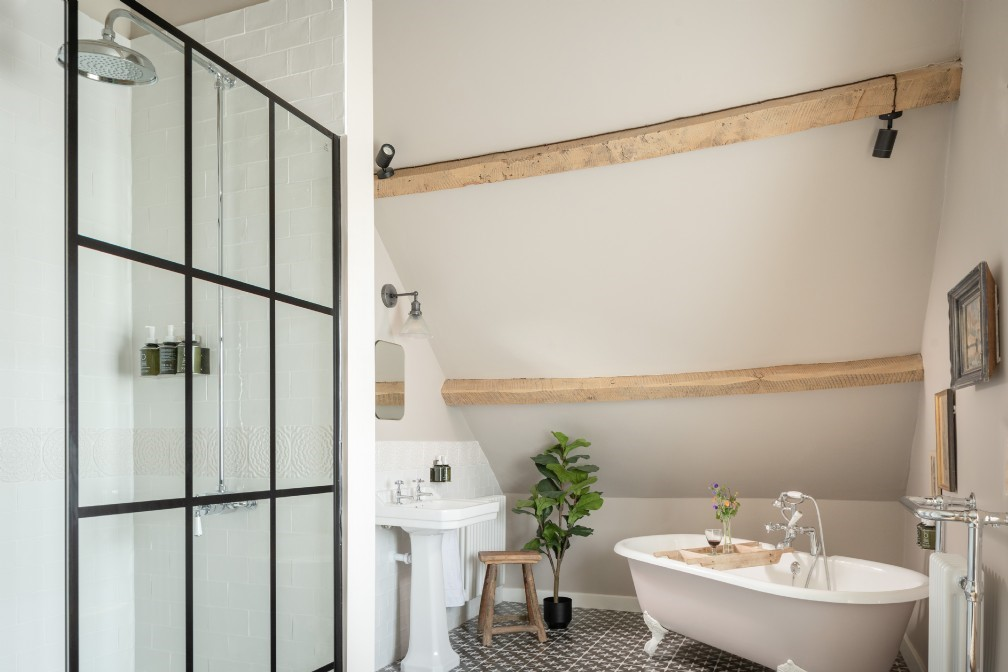 The en suite features a roll top bath and shower